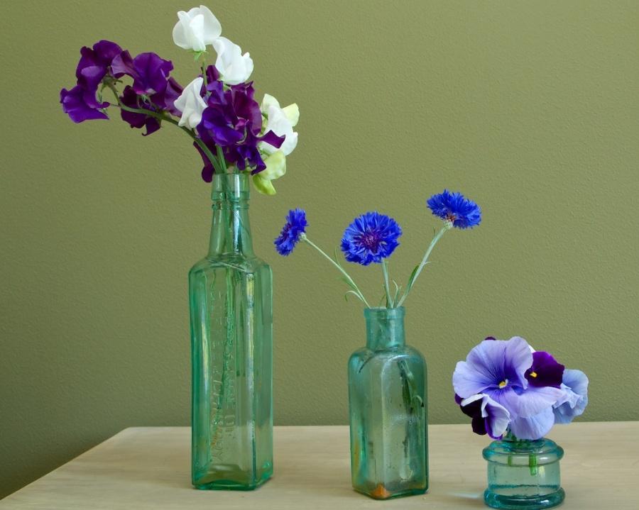 fresh flowers old green bottles